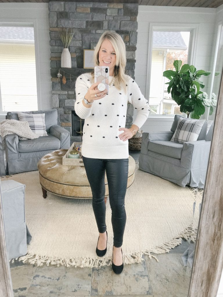 Lifestyle blogger, The Barely B's, standing in her home wearing a Loft black pom-pom sweater and faux leather leggings