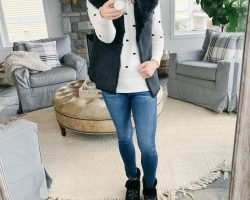 Lifestyle blogger, The Barely B's, standing in her home wearing a Loft faux reversible suede vest, Loft pom-pom sweater, AG jeans, and ugg boots