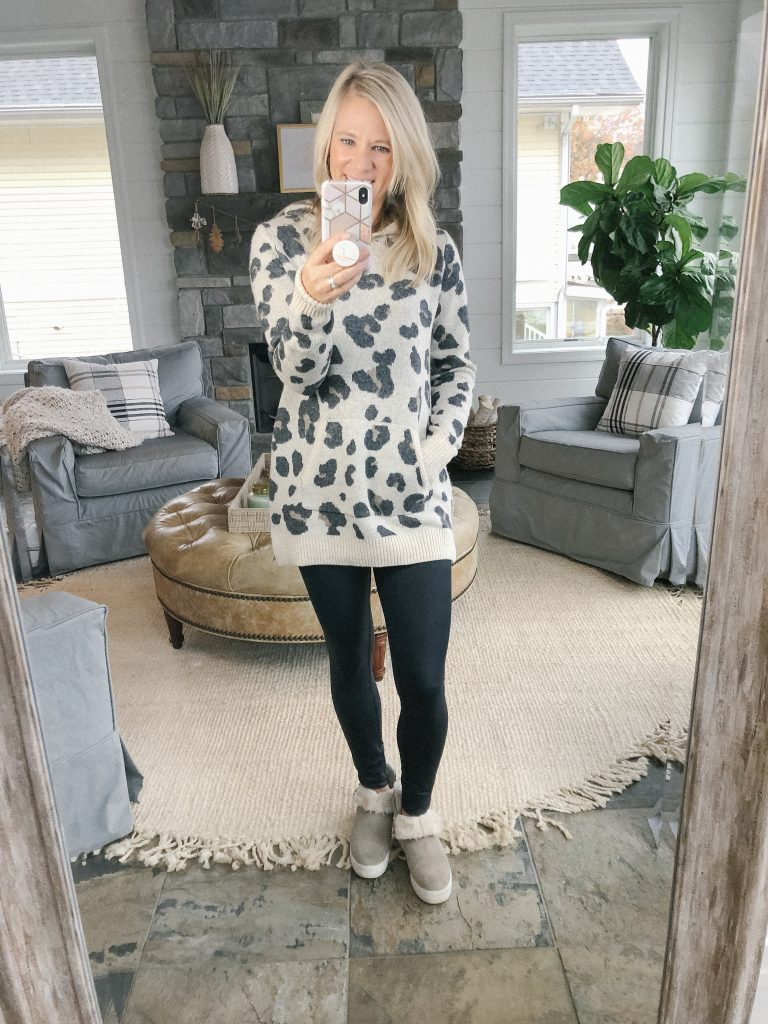 Lifestyle Blogger, The Barely B's, standing in her home wearing a leopard sweater from Loft and black leggings