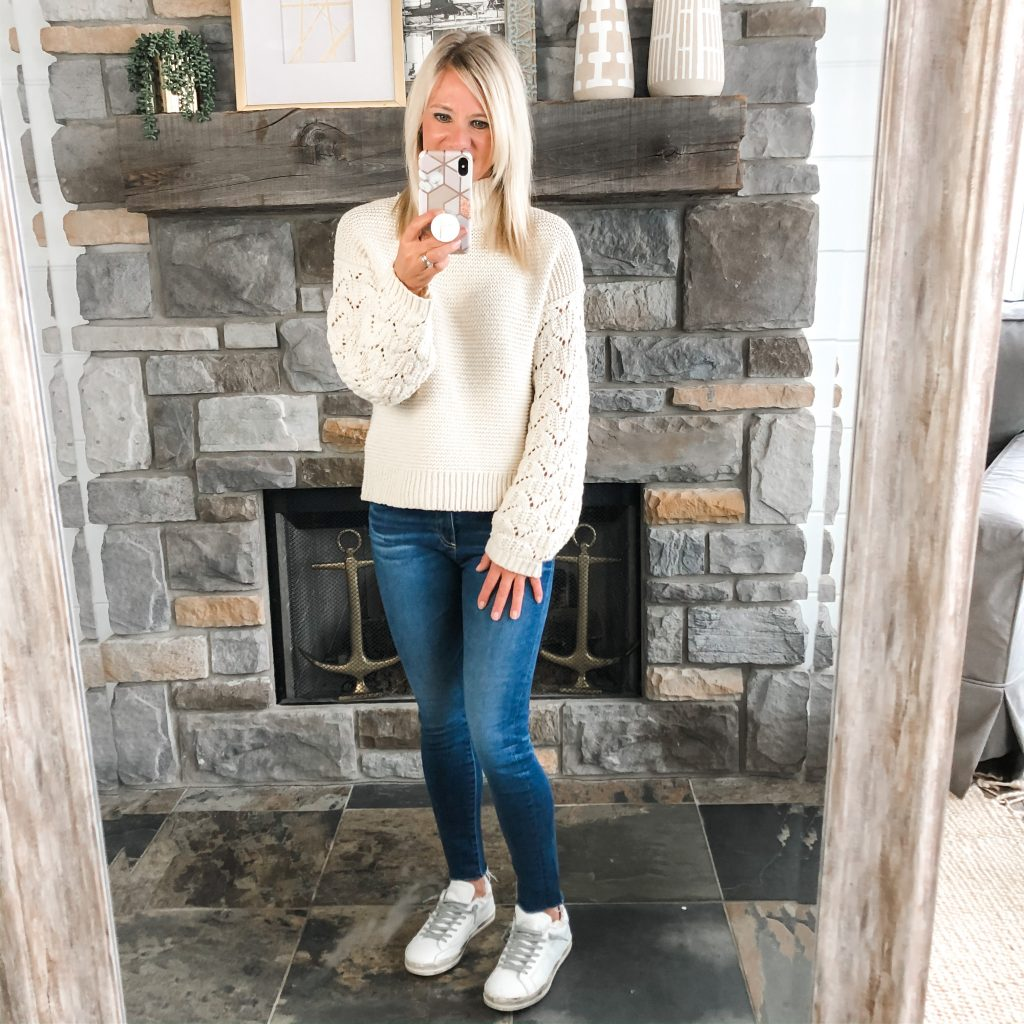 Lifestyle blogger, The Barely B's, wearing a Target cream sweater, blue jeans, and p448 sneakers