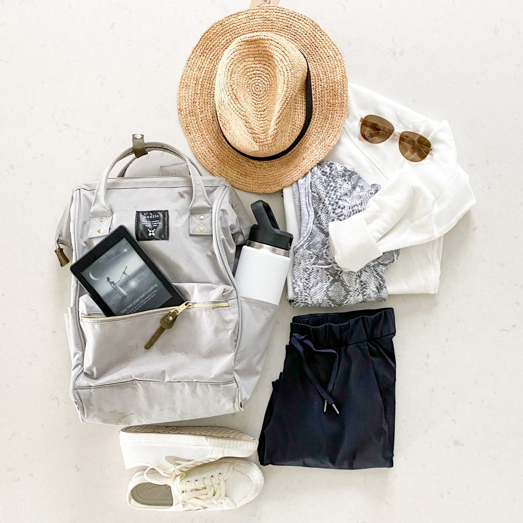 flatly picture of travel day essentials including a backpack, Kindle, Yeti water bottle, sun hat, and sunglasses